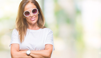 Middle age hispanic woman wearing fashion sunglasses over isolated background happy face smiling with crossed arms looking at the camera. Positive person.