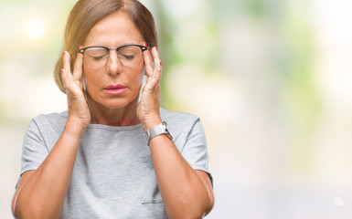 Middle age senior hispanic woman wearing glasses over isolated background with hand on head for pain in head because stress. Suffering migraine.