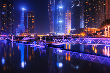 Beautiful view to Dubai Marina, UAE. Luxury yachts at pier. Long exposure time lapse effect at night