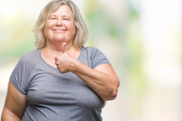 Senior plus size caucasian woman over isolated background doing happy thumbs up gesture with hand. Approving expression looking at the camera with showing success.