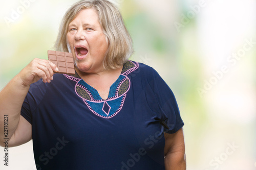 5c9e6bd7c44 Senior plus size caucasian woman eating chocolate bar over isolated  background with a confident expression on smart face thinking serious