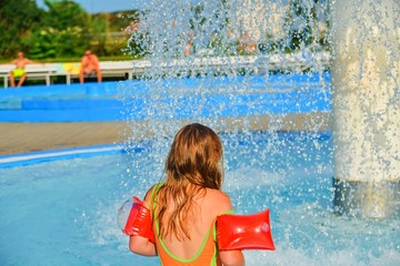 Happy little girl enjoying summer day in the swimming pool. Girl going to a sprinkler in  spray pool. Cute girl with inflatable armbands. Summer and happy chilhood concept
