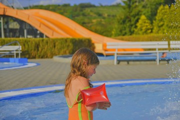 Happy little girl enjoying summer day in the swimming pool. Cute girl with inflatable armbands in small swimming pool.  Summer and happy chilhood concept