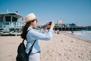 a pretty female tourist taking picture of beach