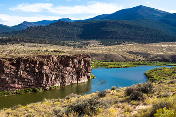 The Green River passes red-brown rock cliffs, wetlands, wide prairies, and mountains in Browns Park National Wildlife Refuge in northwestern Colorado