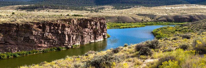 Panorama of the Green River as it passes by red-brown rock cliffs, wetlands, wide prairies, and mountains in Browns Park National Wildlife Refuge in northwestern Colorado