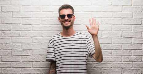 Young adult man wearing sunglasses standing over white brick wall showing and pointing up with fingers number five while smiling confident and happy.