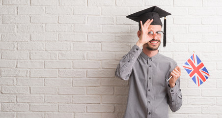 Young adult man over brick wall wearing graduation cap holding uk flag with happy face smiling doing ok sign with hand on eye looking through fingers