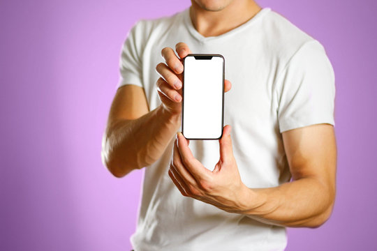 A man holding a black smartphone with a white blank screen. Smartphone with large screen. Close up. Isolated background