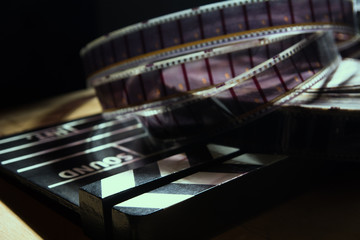 Movie clapper and film reel on a background