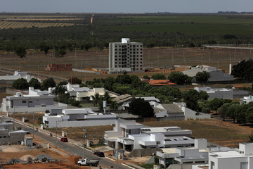 An overview of an upscale neighborhood with many undergoing constructions, and a farm in the background, in Luis Eduardo Magalhaes