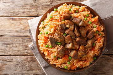 Mexican traditional food: rice cooked with tomatoes, green peas and carrots served fried pork closeup. horizontal top view