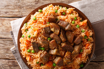 Mexican cuisine: spicy rice cooked with vegetables with tomato sauce and roasted pork close-up. Horizontal top view