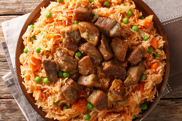Authentic Mexican rice with green peas and carrots served with spicy pork close-up on a plate. horizontal top view