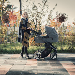 A young mother with a stroller walks through the autumn park. Walking with an infant in the open air in a pine forest. Newborn, family, child, parenthood.
