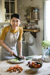Woman cutting green onions in the kitchen
