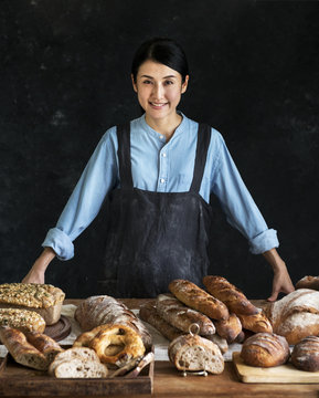 Japanese baker with an assortment of fresh bread