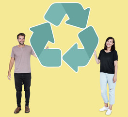 People holding a green recycling symbol