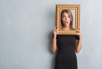Beautiful young woman over grunge grey wall holding vintage frame scared in shock with a surprise face, afraid and excited with fear expression