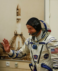 International Space Station (ISS) crew member and astronaut Nick Hague of the U.S. waves after donning a space suit shortly before a launch at the Baikonur Cosmodrome