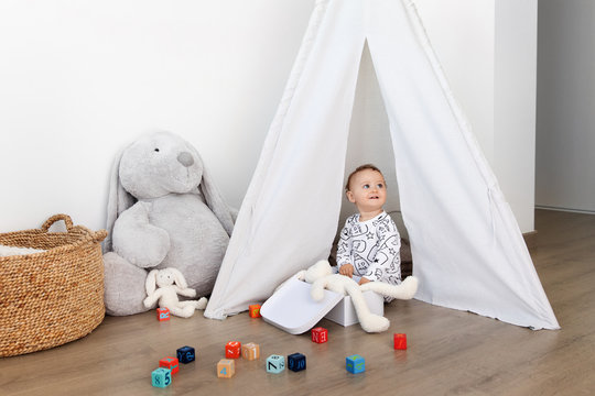 Cute baby playing in teepee