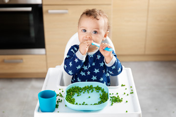 Baby in high chair eating peas with spoon