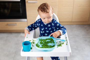 baby in high chair touching peas with finger