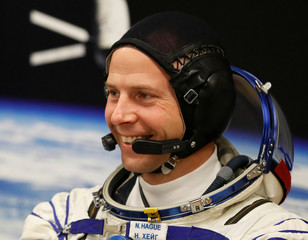 International Space Station (ISS) crew member and astronaut Nick Hague of the U.S. smiles after donning a space suit shortly before a launch at the Baikonur Cosmodrome