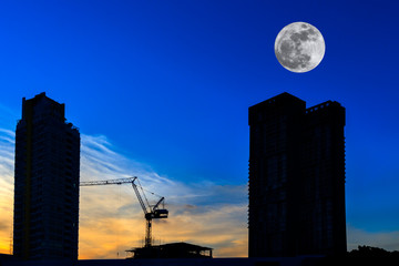 Silhouette two high buildings construction site and tower crane on blue sky and full moon at sunset time. Beautiful background and copy space.