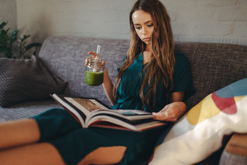 young woman drinking smoothie on couch