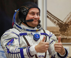 The International Space Station (ISS) crew member cosmonaut Alexey Ovchinin of Russia gestures after donning a space suit shortly before a launch at the Baikonur Cosmodrome