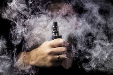 man on a black background close-up with vape hand surrounded by smoke