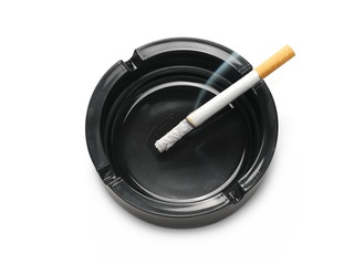 Lit cigarette in black ashtray isolated on white background