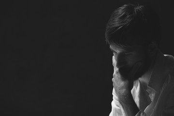 Black and white portrait of handsome worried man, photo with copy space on dark background
