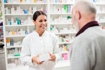 Photo sur Aluminium Pharmacie Medicine, pharmaceutics, health care and people concept - Happy female pharmacist giving medications to senior male customer