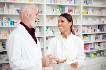 Medicine, pharmaceutics, health care and people concept - Young female and senior male pharmacists smiling and standing in front of shelves with medications