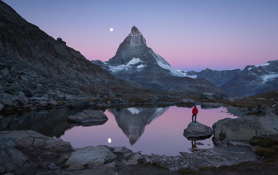 Hiker on a rock in the Riffelsee at dawn, enjoying the Matterhorn view.