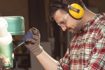 Worker with protective headphones working with a manual wood press