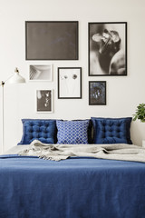Mock-up picture gallery on a white wall above a large bed with navy blue bedding in a bright and modern bedroom interior