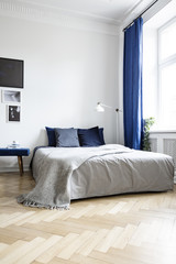 Low angle view of a cozy double bed in a corner of a bright bedroom interior with navy blue textiles and herringbone parquet floor