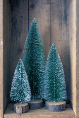 three Christmas tree objects in a wooden box
