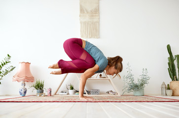 fitness, people and healthy lifestyle concept - young woman doing crane pose at yoga studio