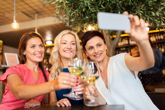 people, technology and lifestyle concept - women drinking wine and taking selfie by smartphone at bar or restaurant