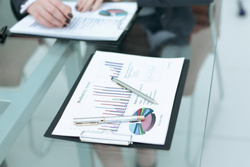 pens and financial report on the glass table in the office