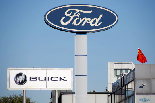 Chinese national flag flies on the roof of a car dealership near the brand logos of carmakers Ford and Buick in Beijing