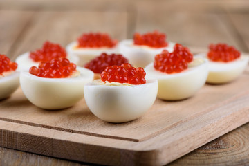 Rustic style. Red caviar on halves of hard-boiled chicken eggs on a cutting board