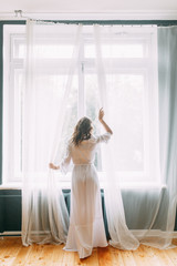 Conceptual wedding, the morning of the bride in the European style. Boudoir dress and a bouquet of flowers, fees in the interior Studio. White minimalism for the bride