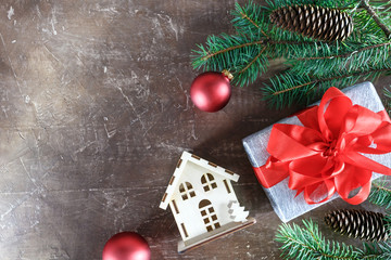 Christmas background decorations with gift boxes, red christmas decoration on the xmas tree  and new house on wooden background with copy space