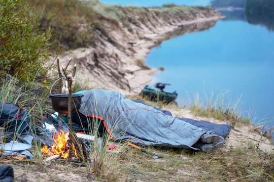 A man is sleeping next to a fire at the beach dunes.