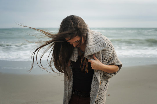 Fashion pensive woman portrait walking alone on a sea beach